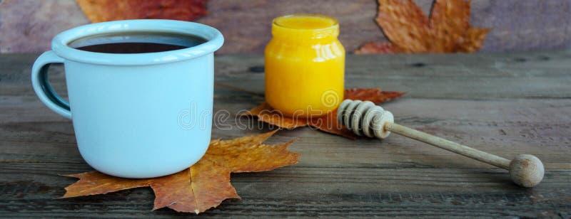 Um copo do chá perto do lenço morno feito malha rústico do outono ou do inverno no fundo de madeira marrom foto de stock royalty free