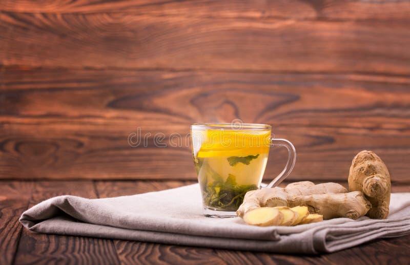 Um copo do chá Um copo em um fundo de madeira Um copo bonito com limão cortado e raiz orgânica do gengibre Copie o espaço foto de stock