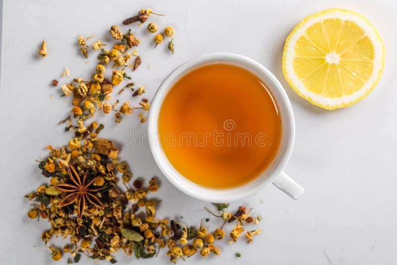 Um copo do chá verde com as flores secadas da camomila e uma fatia de limão cortado em um fundo branco Dieta e bebida saudável fl fotos de stock