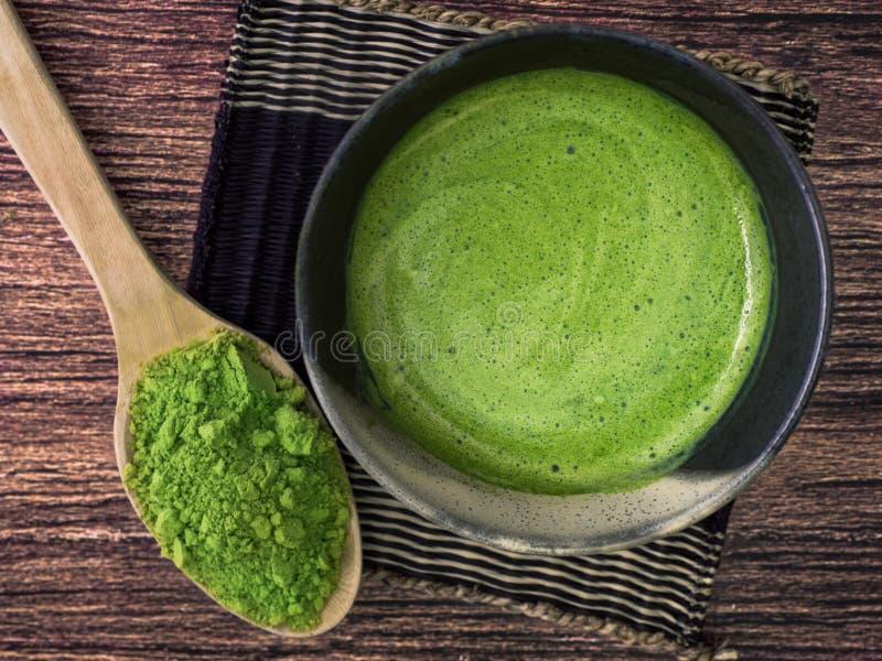 Um copo do latte do chá verde no pó de bambu da esteira e do matcha na colher no fundo de madeira imagem de stock