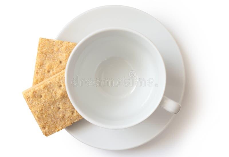 Um copo e uns pires cerâmicos brancos vazios com o biscoito amanteigado dois quadrado fotografia de stock