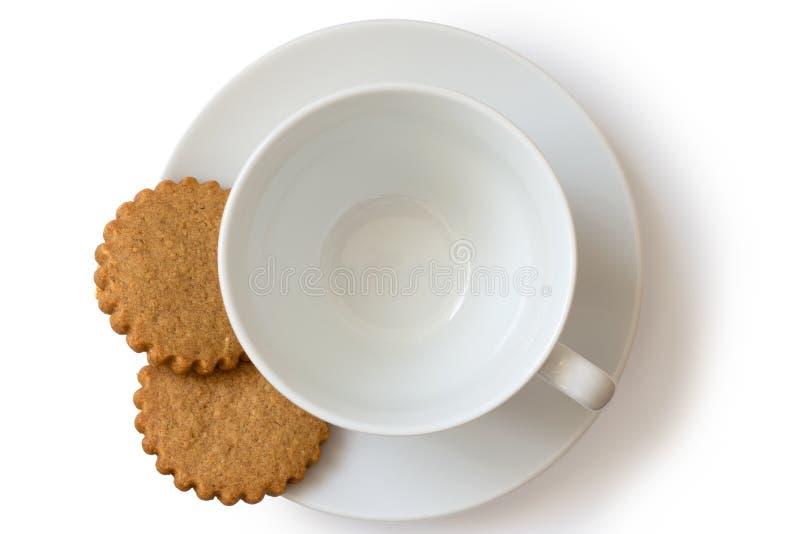 Um copo e uns pires cerâmicos brancos vazios com o biscu de dois pão-de-espécie fotografia de stock royalty free