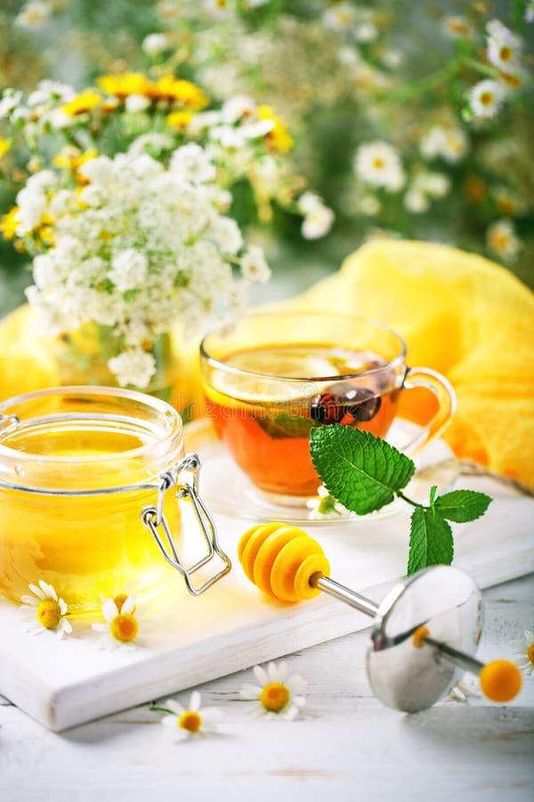 Um copo saudável do chá, um frasco do mel e flores Foco seletivo imagens de stock royalty free