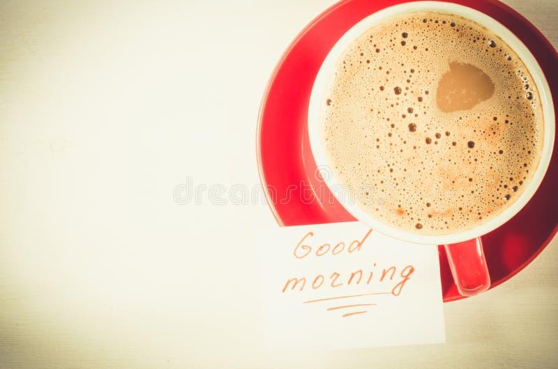 Um copo vermelho do bom dia do cappuccino e das notas na tabela rústica clara imagem de stock
