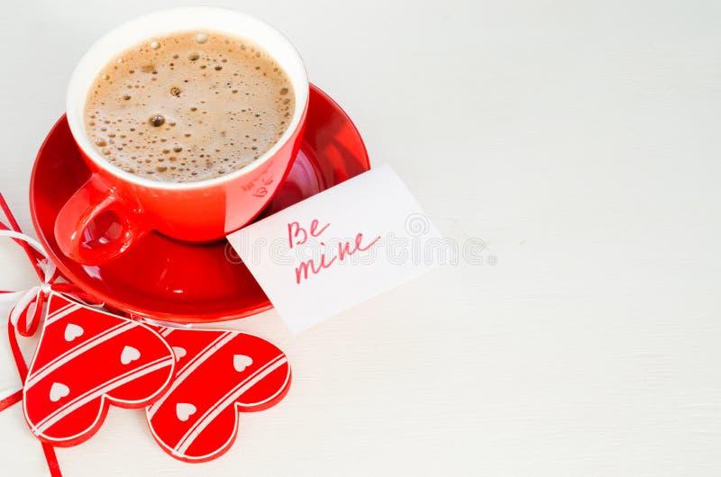 Um copo vermelho do cappuccino com coração de madeira e das notas seja o meu imagens de stock royalty free