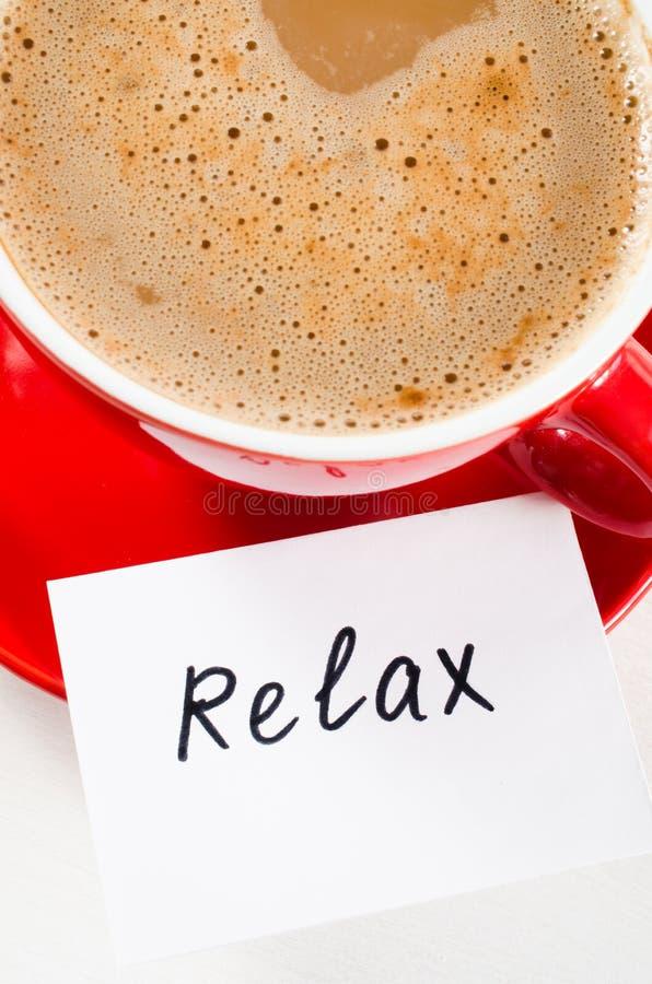 Um copo vermelho do cappuccino e as notas relaxam na tabela rústica clara imagens de stock royalty free