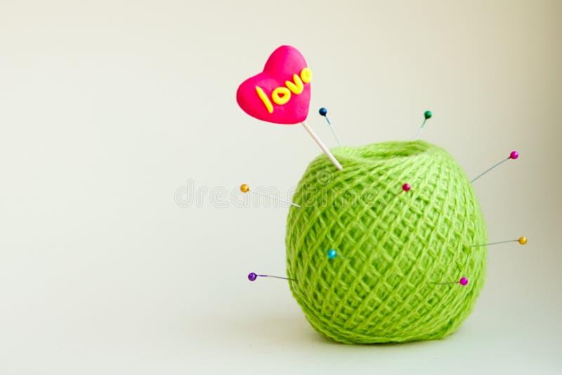 Um coração cor-de-rosa caseiro no palito, doces, massa, linhas verdes de lãs do clube, o dia de Valentim, como Apple, um cacto imagem de stock royalty free