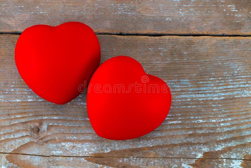Um coração de dois vermelhos no fundo de madeira foto de stock