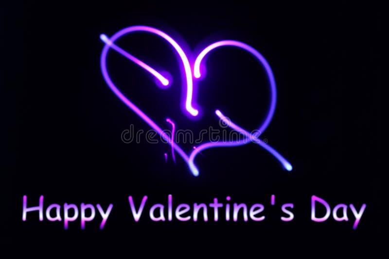Um coração de incandescência de néon e um dia feliz do ` s do Valentim da inscrição sobre foto de stock royalty free