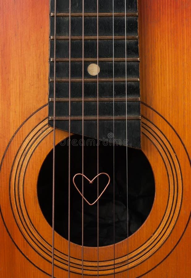 Um coração encontra-se em cordas a guitarra imagens de stock royalty free