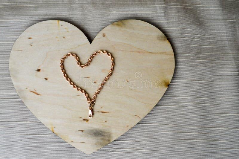 Um coração feito de uma corrente fêmea em um bonito, vintage do ouro, coração caseiro, de madeira ao dia do ` s do Valentim foto de stock