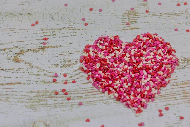 Um coração grande feito dos corações pequenos coloridos No fundo de madeira, bokeh da foto Feriado do dia do ` s do Valentim Cart imagem de stock