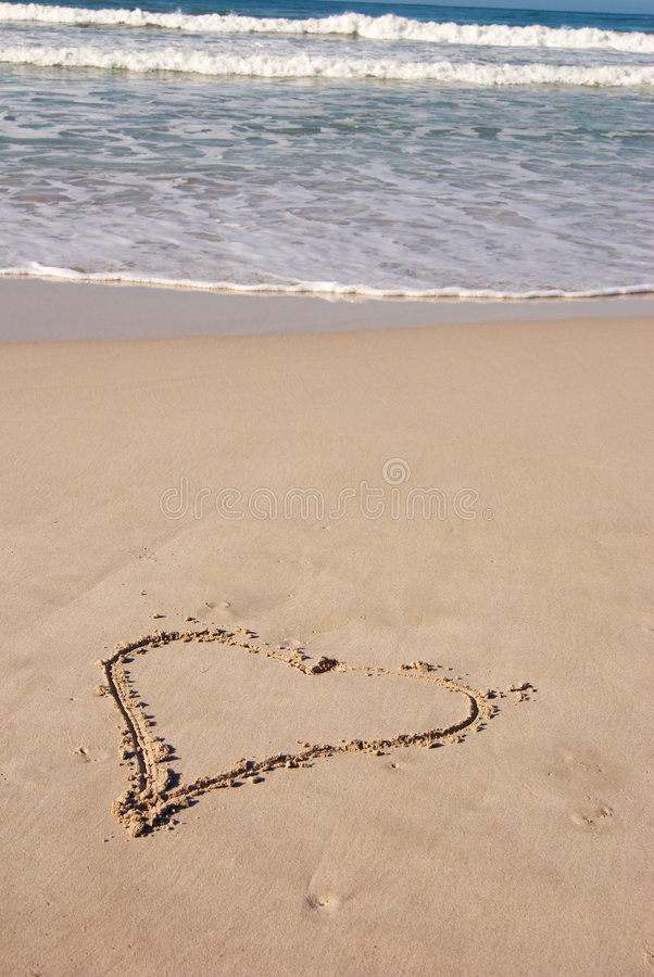 Um coração na praia arenosa imagens de stock