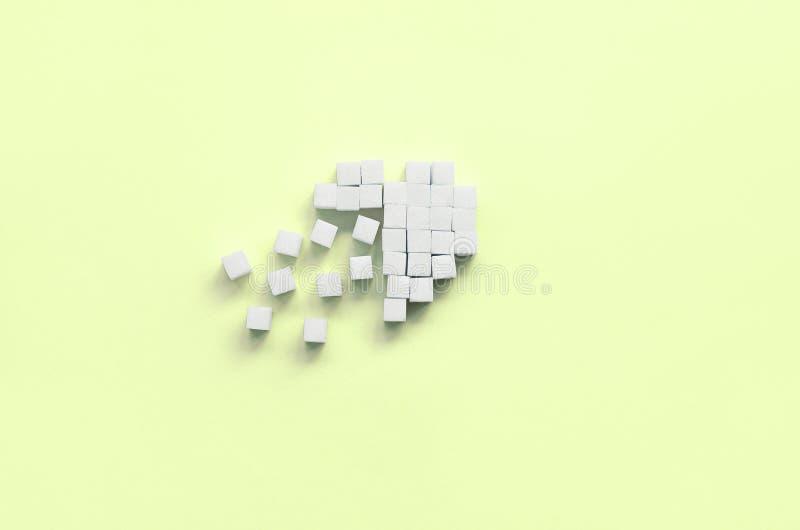 Um coração quebrado feito de cubos do açúcar encontra-se em um cal pastel na moda imagens de stock