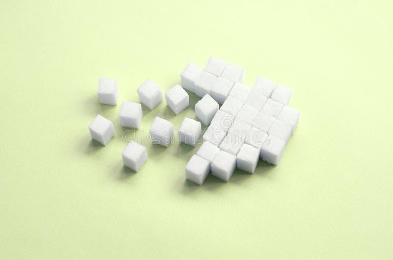 Um coração quebrado feito de cubos do açúcar encontra-se em um cal pastel na moda fotografia de stock