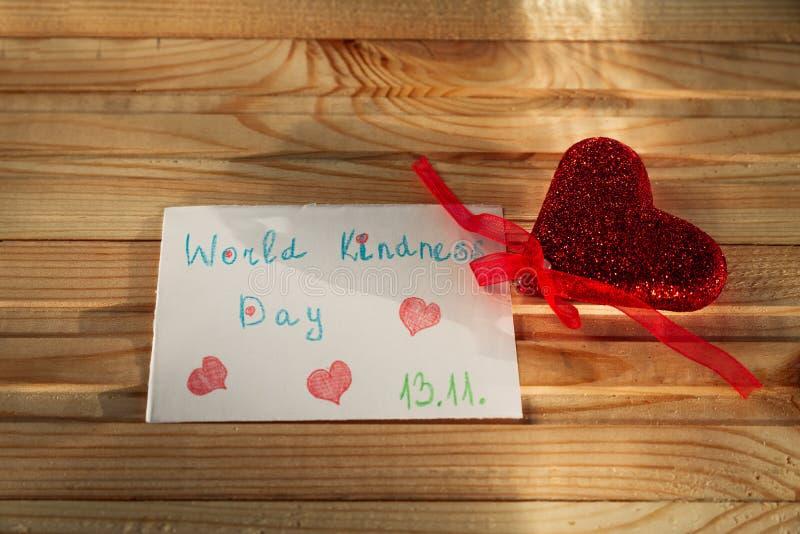 Um coração vermelho com uma nota sobre o dia da bondade do mundo encontra-se na tabela de madeira foto de stock royalty free
