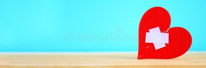 Um coração vermelho de feltro quebrado em duas metades, coladas junto por um emplastro em uma tabela de madeira em um fundo azul fotografia de stock