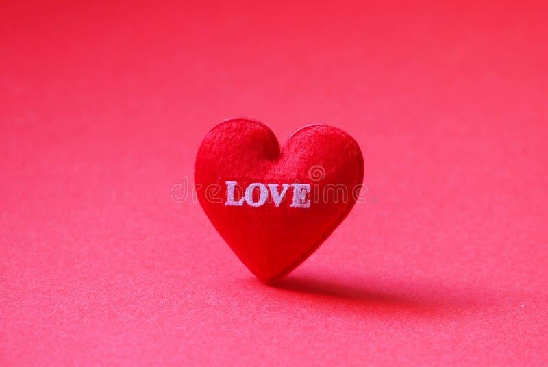 Um coração vermelho deu forma com amor no fundo vermelho foto de stock royalty free