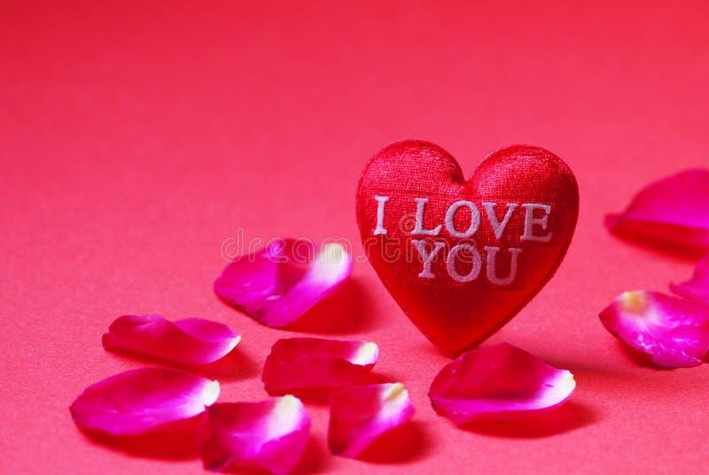 Um coração vermelho deu forma com as pétalas eu te amo e de Rosa no fundo vermelho fotos de stock royalty free