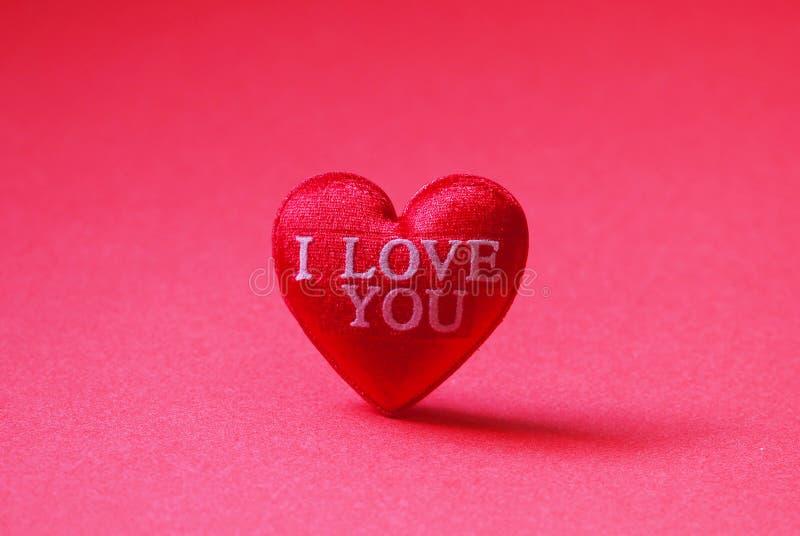 Um coração vermelho deu forma com eu te amo no fundo vermelho imagens de stock