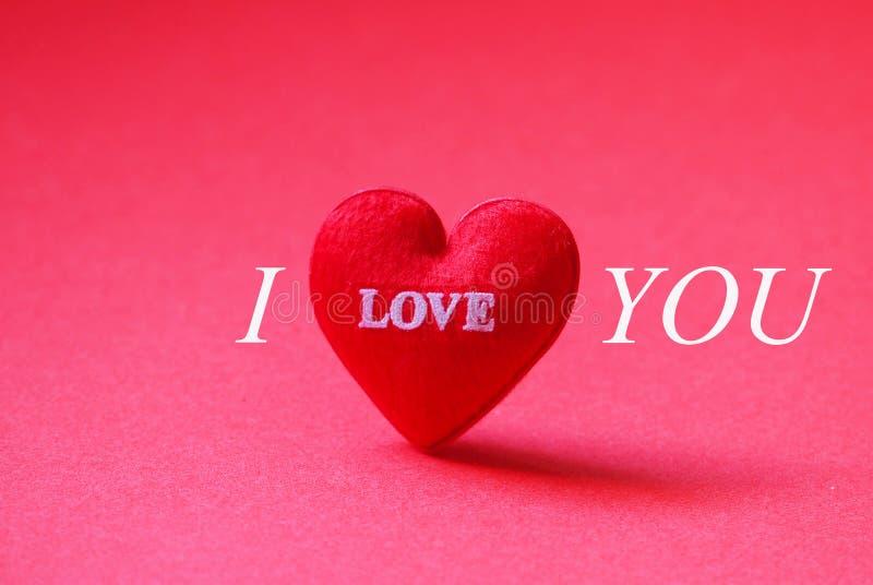 Um coração vermelho deu forma com eu te amo no fundo vermelho fotos de stock royalty free