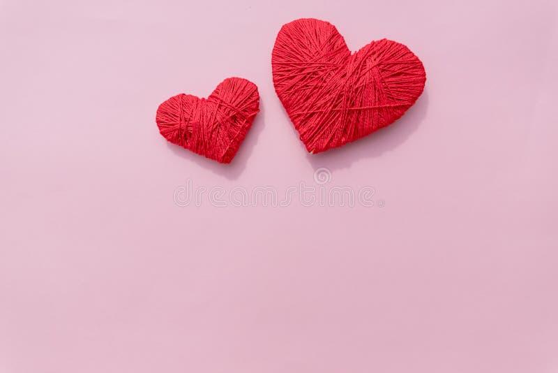 Um coração vermelho orgânico feito crochê feito a mão de lãs a bola do fio de dois vermelhos gosta de um coração no fundo cor-de- foto de stock royalty free