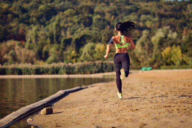 Um corredor da menina dos esportes corre ao longo da costa do lago que movimenta-se imagem de stock royalty free