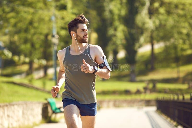 Um corredor masculino dos jovens movimenta-se no parque imagens de stock