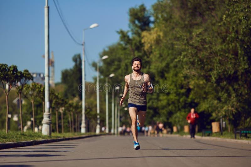 Um corredor masculino dos jovens movimenta-se no parque fotos de stock