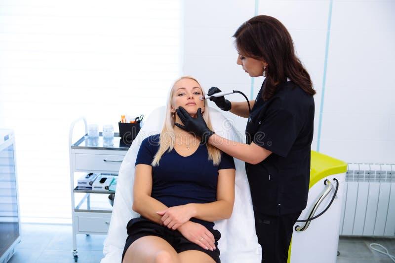 Um cosmetologist realiza procedimentos na cara do paciente com um instrumento da hidro-casca Limpeza e rejuvenescimento imagens de stock
