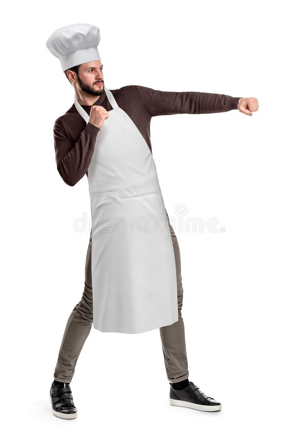 Um cozinheiro chefe bonito novo em um chapéu e em um avental do cozinheiro chefe que levantam com punhos apertados e saiu à mão p imagens de stock royalty free