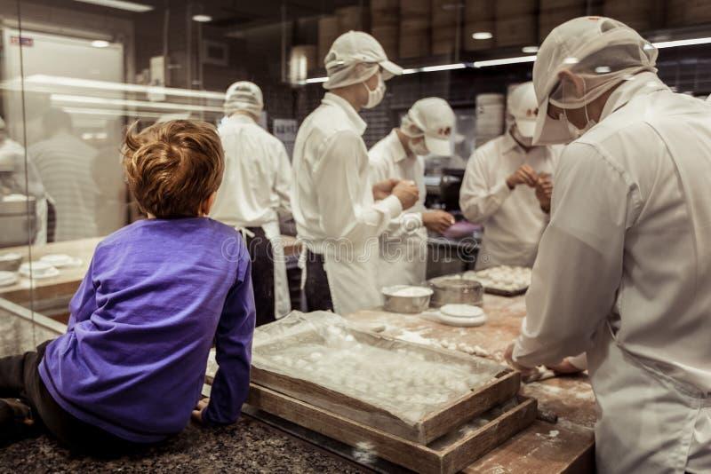 Um cozinheiro chefe de observação da janela nova do menino que faz bolinhas de massa chinesas imagens de stock royalty free
