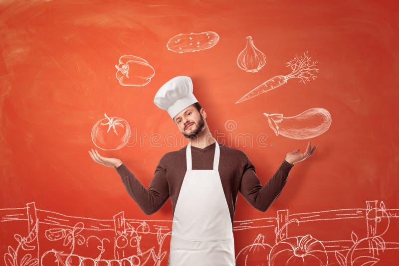 Um cozinheiro chefe novo agradável em um chapéu e em um avental do cozinheiro chefe que fazem um gesto de apresentação em imagens imagem de stock royalty free