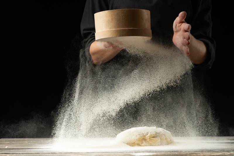 Um cozinheiro chefe profissional em uma cozinha profissional prepara a massa da farinha para cozinhar a massa de Italian, pizza,  fotografia de stock royalty free