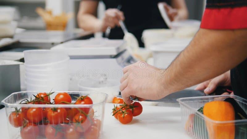 Um cozinheiro chefe que trabalha na cozinha Cortando os tomates de cereja foto de stock
