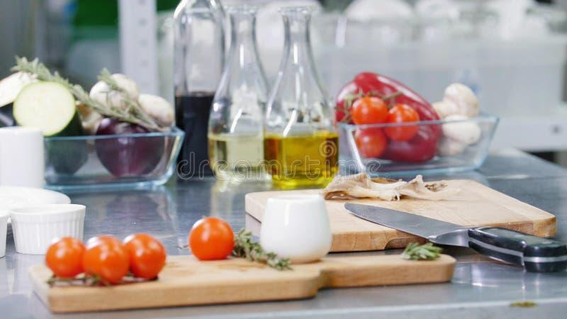 Um cozinheiro chefe que trabalha na cozinha Uma tabela do local de trabalho E imagens de stock royalty free