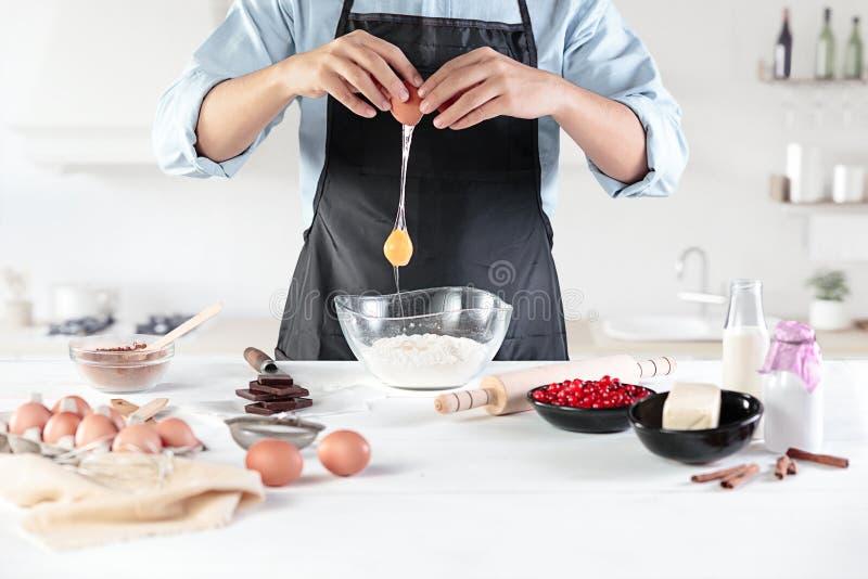 Um cozinheiro com ovos em uma cozinha rústica na perspectiva das mãos do ` s dos homens fotografia de stock royalty free