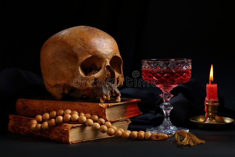 Um crânio, um rosário, um vidro do vinho e uma vela ardente fotografia de stock