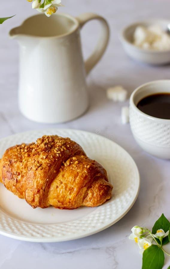 Um croissant e um caf? em um fundo de m?rmore As flores Pequeno almo?o imagem de stock royalty free