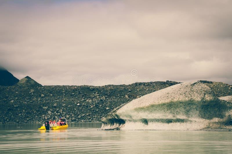 Um cruzeiro amarelo da geleira do barco no lago Tasman com efeitos da cor do vintage foto de stock