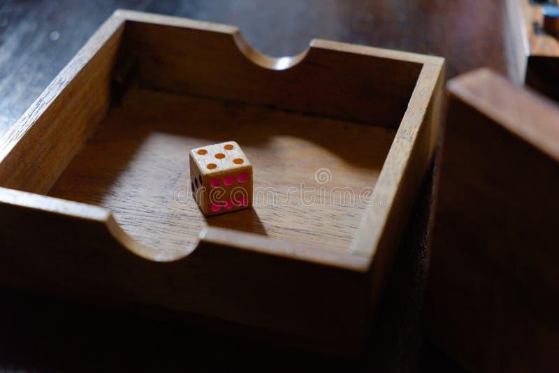 Um dado de madeira na caixa fotografia de stock royalty free