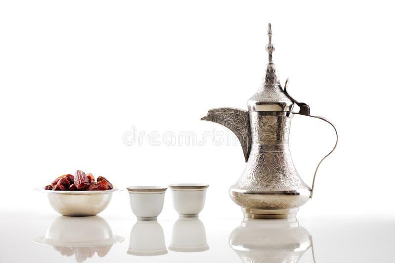 Um dallah, um potenciômetro do metal para fazer o café árabe com uma bacia de datas secadas fotografia de stock royalty free