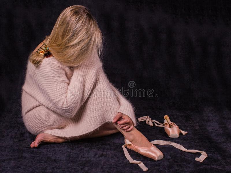Um dançarino de bailado cansado que senta-se no assoalho no backgrou escuro imagem de stock