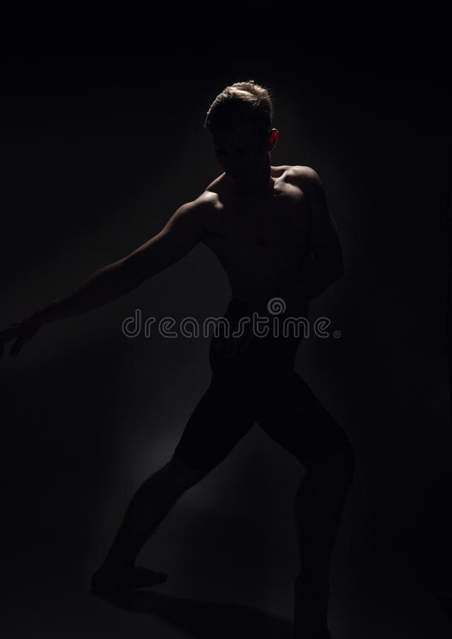 Um dançarino de bailado, fundo do preto escuro, backlighting backlit imagem de stock