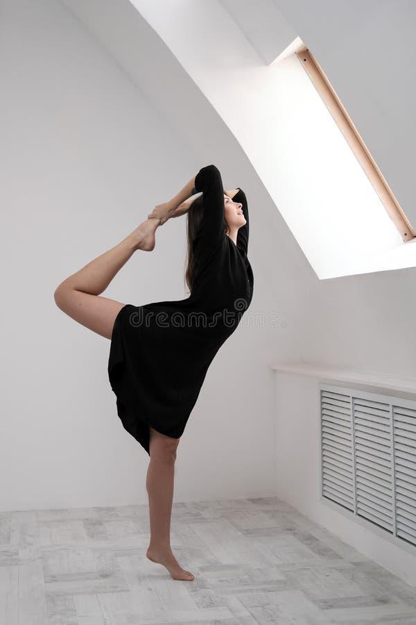 Um dançarino fêmea novo em um vestido preto está esticando pela janela Salão branco, a classe trabalhadora, asanas da ioga imagem de stock