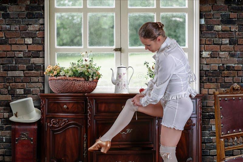 Um dançarino que ajusta suas meias perto do armário fotos de stock