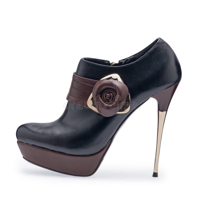 Um de estiletes do preto e do marrom de sapatas das mulheres com uma correia decorativa fotos de stock royalty free