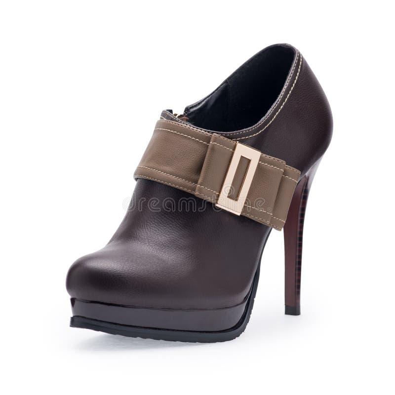 Um de estiletes marrons das sapatas das mulheres com curvatura do metal imagem de stock