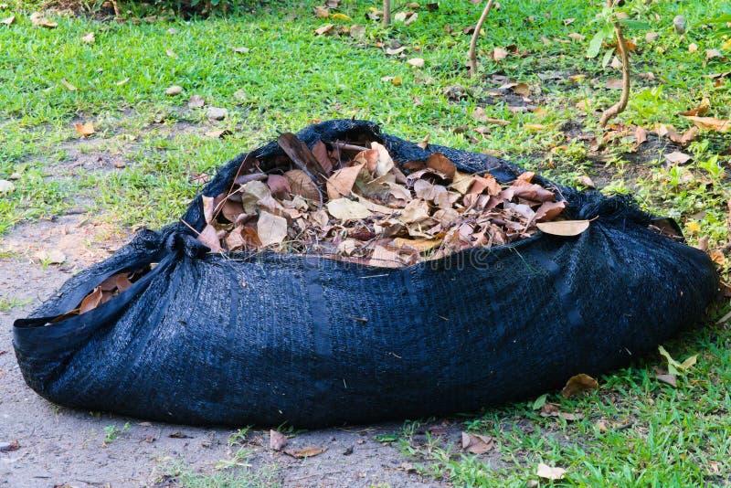 Um de vista completa de um encerado tecido plástico preto, enchido com as folhas marrons, deteriorando foto de stock