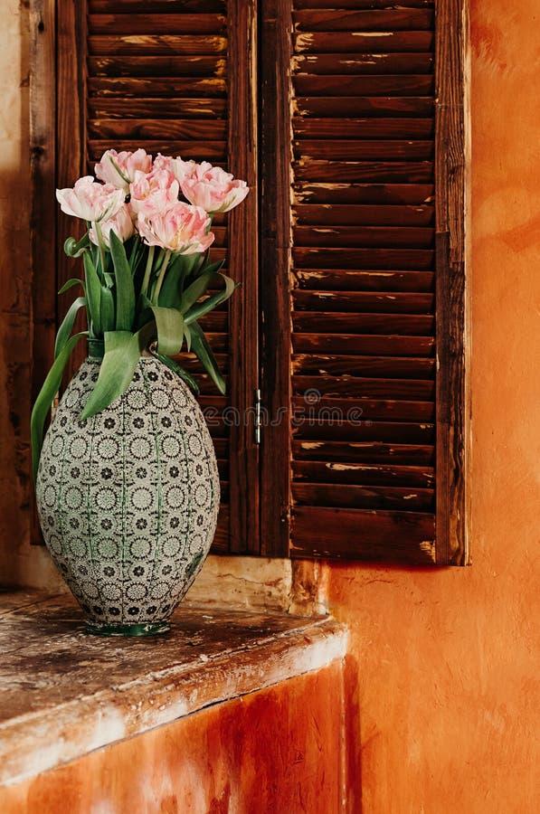 Um delicado centrou-se o ramalhete das flores em um vaso velho sobre um sil da janela imagens de stock royalty free
